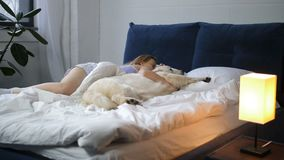 Женщина и ее собака лучшего друга спать в кровати сток-видео