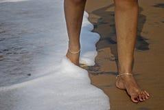 Женщина идет на воду моря на пляже Стоковые Фото