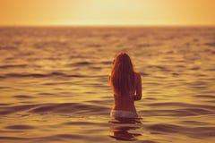 Женщина идет для заплыва во время захода солнца Стоковая Фотография RF