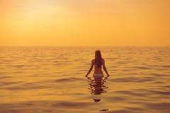 Женщина идет для заплыва во время захода солнца Стоковые Изображения