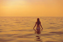 Женщина идет для заплыва во время захода солнца Стоковые Фотографии RF