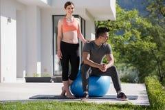 Женщина и личный тренер делая тренировку с шариком pilates Стоковые Изображения