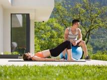 Женщина и личный тренер делая тренировку с шариком pilates Стоковые Фото