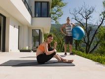 Женщина и личный тренер делая тренировку с шариком pilates Стоковое Изображение RF