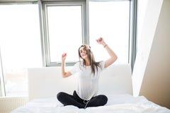 женщина или девочка-подросток в наушниках слушая к музыке от smartphone и танцуя на кровати дома Стоковые Фотографии RF