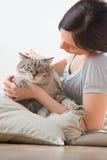 Женщина и кот ослабляя на подушках на поле Стоковое Изображение