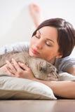 Женщина и кот ослабляя на подушках на поле Стоковые Изображения RF