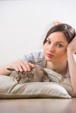 Женщина и кот ослабляя на подушках на поле Стоковое Фото