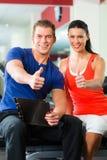 Женщина и личный тренер в спортзале, с гантелями Стоковые Изображения