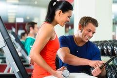 Женщина и личный тренер в спортзале, с гантелями Стоковое фото RF