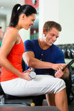 Женщина и личный тренер в спортзале, с гантелями Стоковое Изображение