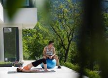 Женщина и личный тренер делая тренировку с шариком pilates Стоковое Изображение