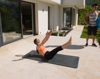 Женщина и личный тренер делая тренировку с шариком pilates Стоковое Фото