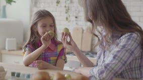 Женщина и маленькая девочка держа пасхальные яйца и показывая их друг к другу близкие вверх Подготовка на праздник пасхи акции видеоматериалы