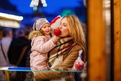 Женщина и маленькая девочка есть crystalized яблоко на метке рождества Стоковое Изображение