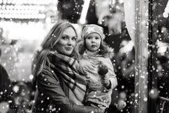Женщина и маленькая девочка есть crystalized яблоко на метке рождества Стоковые Фотографии RF