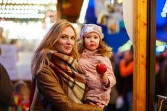 Женщина и маленькая девочка есть crystalized яблоко на метке рождества Стоковая Фотография