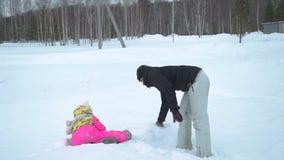Женщина и маленькая девочка имея потеху со снегом сток-видео