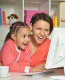 Женщина и маленькая девочка используя компьютер Стоковая Фотография RF