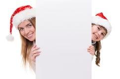 Женщина и маленькая девочка нося шлем Дед Мороз Стоковое Изображение