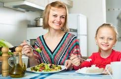 Женщина и маленькая девочка есть на кухне Стоковые Фотографии RF
