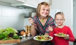Женщина и маленькая девочка есть на кухне Стоковое Изображение