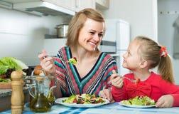 Женщина и маленькая девочка есть на кухне Стоковое Изображение RF