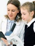 Женщина и маленькая девочка используя микроскоп стоковое изображение