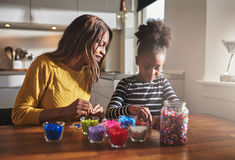Женщина и маленькая девочка создавая вышитые бисером ремесла Стоковые Фото