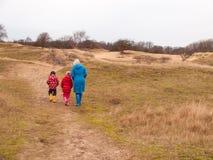 Женщина и 2 малых дет идя в дюны в зиме Стоковые Изображения RF