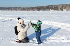 Женщина и мальчик играя на снеге в зиме Стоковые Изображения RF