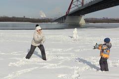 Женщина и мальчик играя снежные комья на речном береге Стоковая Фотография