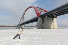 Женщина и мальчик играя снежные комья на речном береге Стоковые Фотографии RF