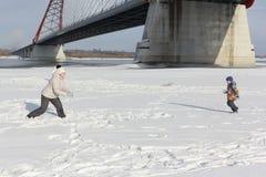 Женщина и мальчик играя снежные комья на речном береге Стоковые Изображения RF