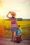 Женщина и мальчик путешествуя с старым чемоданом дальше Стоковые Изображения RF