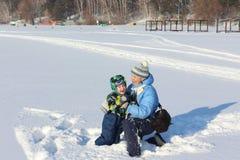 Женщина и мальчик смеясь над на снеге Стоковое Изображение RF