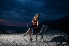 Женщина и мальчик с компьтер-книжкой на пляже Стоковое Изображение
