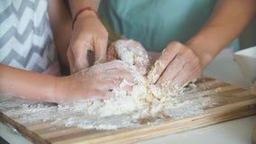 Женщина и милая дочь варя на кухне, делая тесто для дня рождения сток-видео
