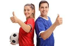 Женщина и мужской футболист держа их большие пальцы руки вверх Стоковые Фото