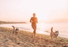 Женщина и осиплый jogging на взморье Стоковые Изображения RF