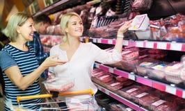 Женщина и дочь выбирая мясо Стоковая Фотография