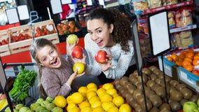 Женщина и дочь покупая плодоовощи Стоковая Фотография RF