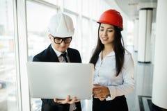 Женщина и предприниматель и архитектор человека в hemlet на деловой встрече, смотря компьтер-книжку на планах здания Стоковое Изображение