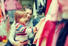 Женщина и ребенок выбирают носку на магазине Стоковые Фотографии RF