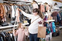Женщина и ребенок выбирая одежды для младенца в магазине Стоковое Изображение RF