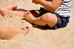 Женщина и ребенок в песке Стоковые Изображения