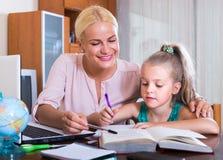 Женщина и ребенок имея урок внутри помещения Стоковое Фото