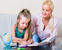 Женщина и ребенок имея урок внутри помещения Стоковые Фото