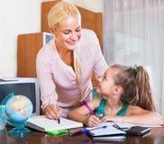 Женщина и ребенок имея урок Стоковое фото RF