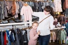 Женщина и ребенок ища одежду для младенца в магазине Стоковая Фотография RF